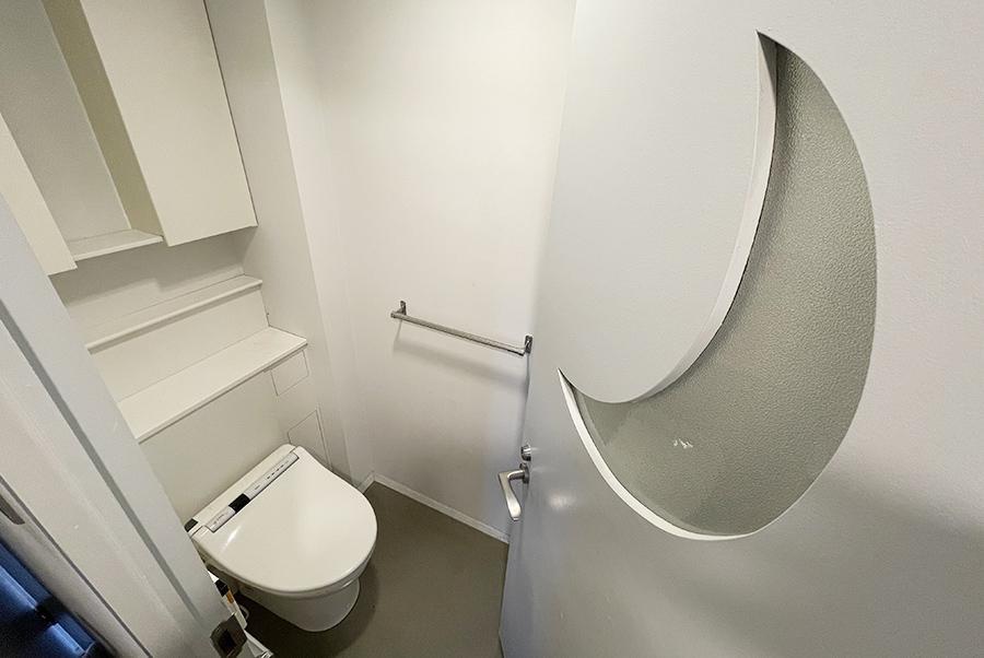 トイレ。月が彫られた個性的な扉。