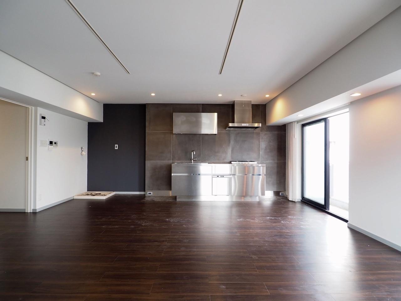 ステンレスのキッチンと黒のタイルがアクセントに。