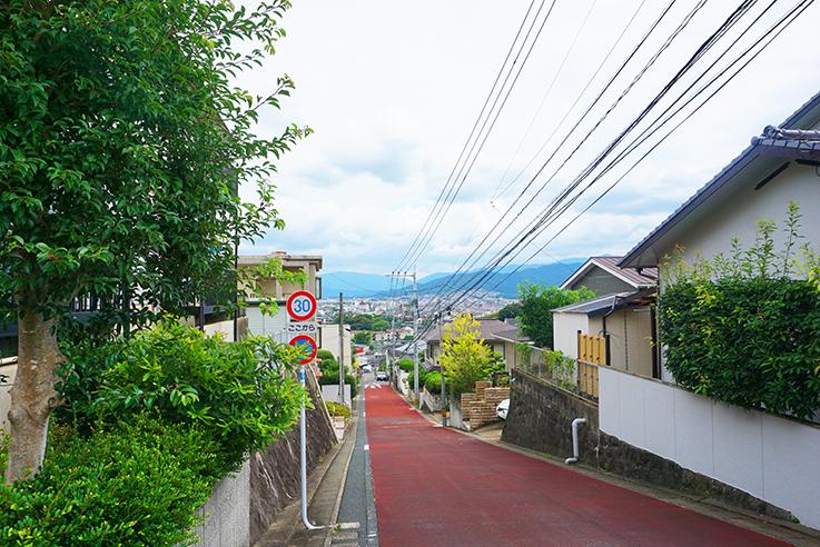マンション前の道路からの眺め。ご覧の通り坂の上にあります。