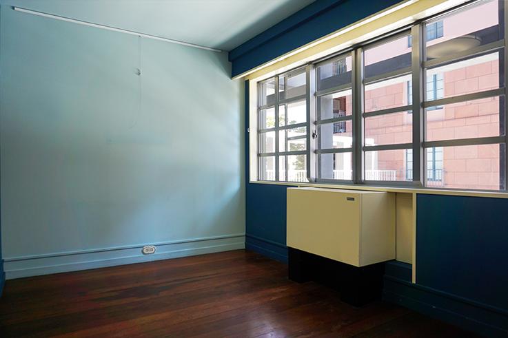 お隣の部屋。青の色使いが鮮やかなお部屋となります。全ての部屋で使用されている床置きタイプの空調はPMACというブランドのもので日本でも購入可能です。