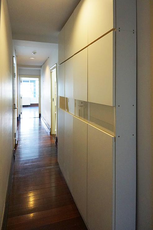 奥の部屋からリビングを眺めた図。長い廊下には薄型収納家具が備え付けられています。