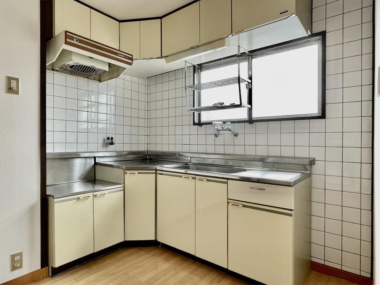 L字のキッチン。換気扇がレトロでレバースイッチ。