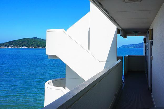 外から戻ってきて共用部廊下を歩くとこの眺望。視界の半分が海です。
