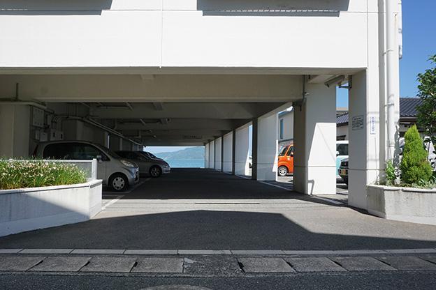 エントランス横の駐車場。先には海が見えています。駐車場には複数空きがありますので、2台以上の契約も可能の様です(2021年10月9日現在)。