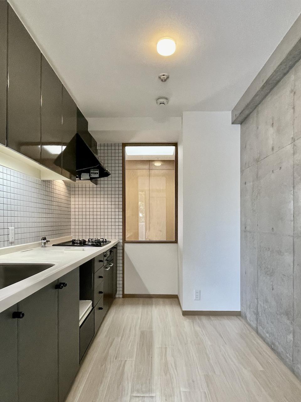 タイルとコンクリートのお洒落なキッチン。ガラスの向こうは階段です。