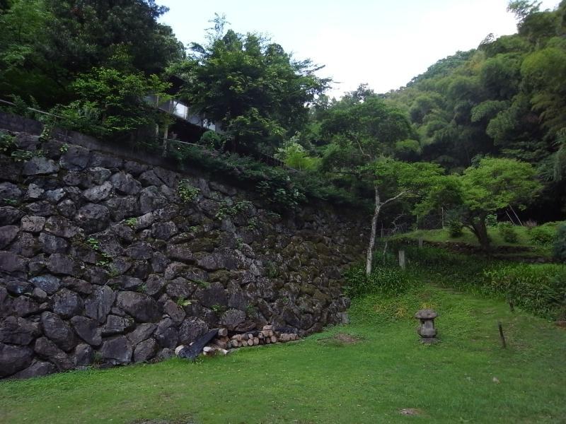 起伏に富む敷地。石垣の上に母屋、手前は来客用駐車スペースで3台ほど駐車可。