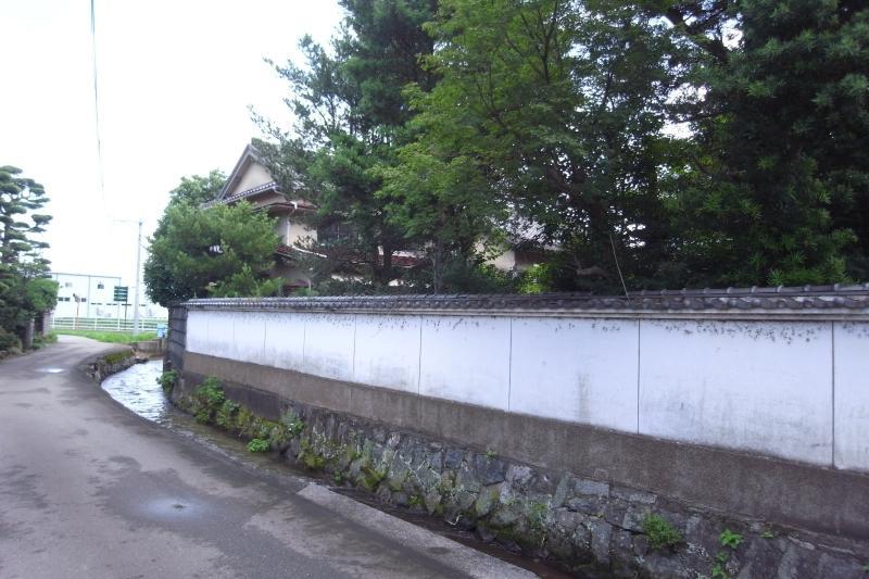 旧道から見ると2階建ての建物の姿がよくわかります。白塀の途中に玄関の門がありますが、今は塞がれています。