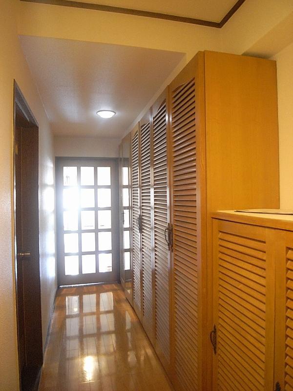 玄関を上がるとすぐにある木目の収納棚。