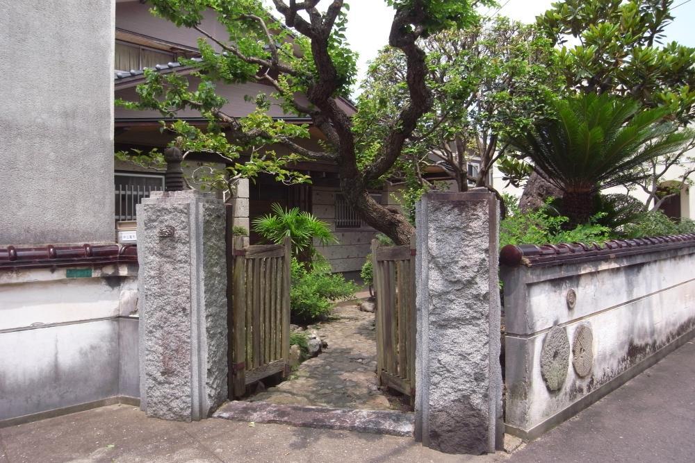 石の門柱に木製の扉。石臼のパーツなどが埋め込まれた塀が楽しげ。