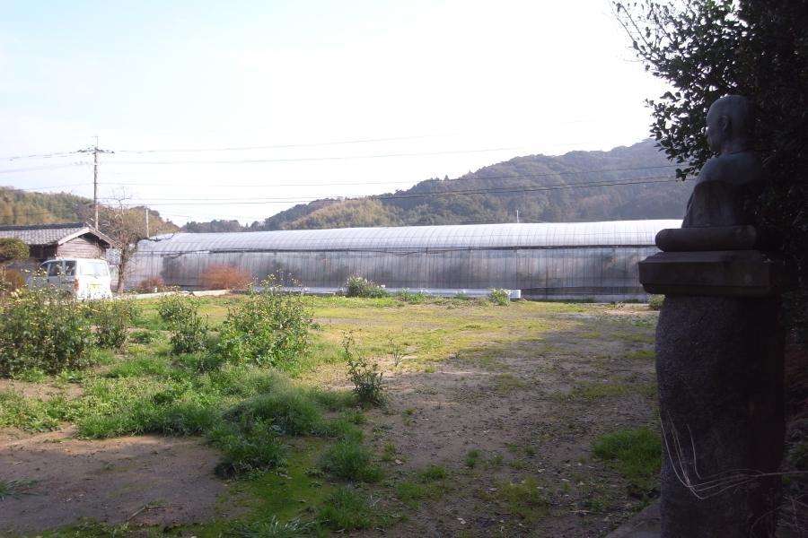 右は敷地内に残る銅像。その視線の先に美しい農村風景が広がります