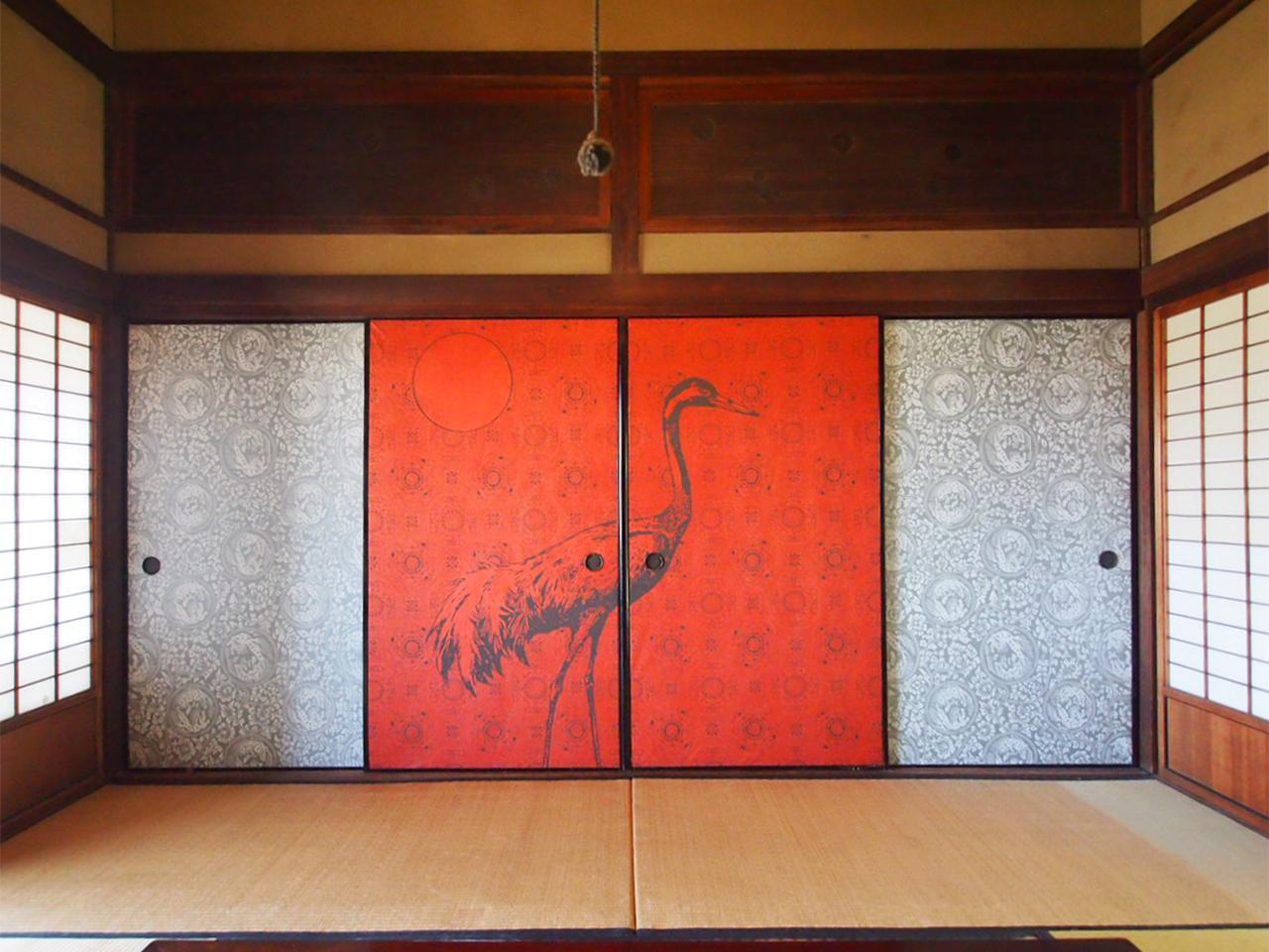 朱色地に鶴と月が描かれた襖 欄間には刀の鍔が。