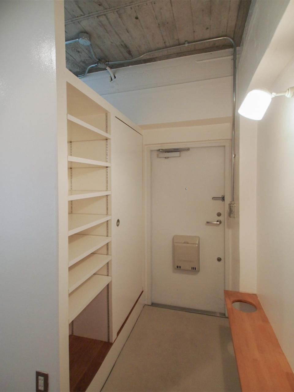 玄関にも棚がいっぱい。まあるい穴は傘立てとして。