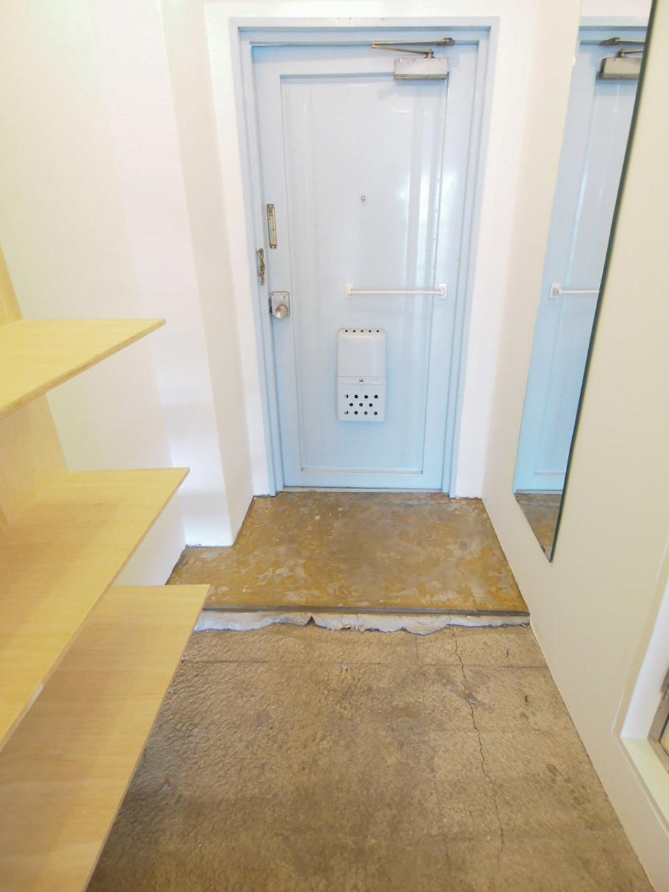 ざっくりとした土間のポーチに水色の玄関扉がキュート