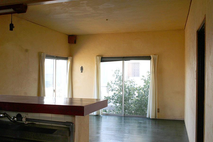 キッチンからリビング。床は緑色、壁はクリーム色です。