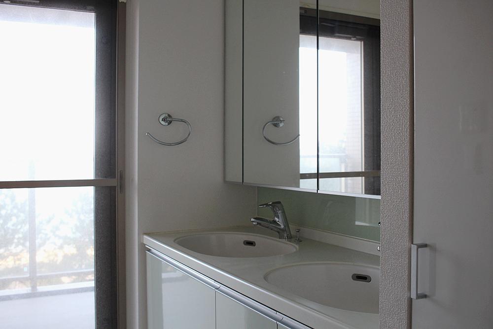 洗濯機置き場と脱衣所、洗面所。海が見えるバルコニーにアクセス。