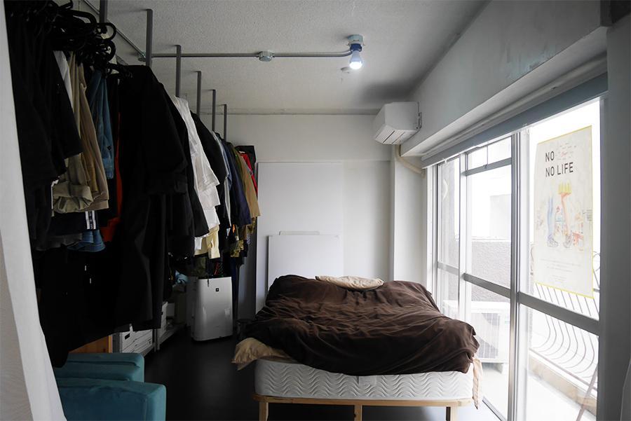 洋服とカーテンで仕切られたベッドスペース。