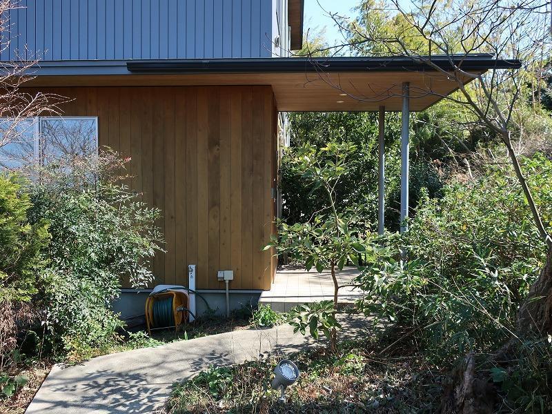 アプローチは伸びやかな庇、周囲の緑、外壁や軒裏の板張りが美しいです。