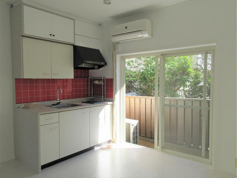 白で仕上げたプレーンな部屋、赤のタイルのキッチン