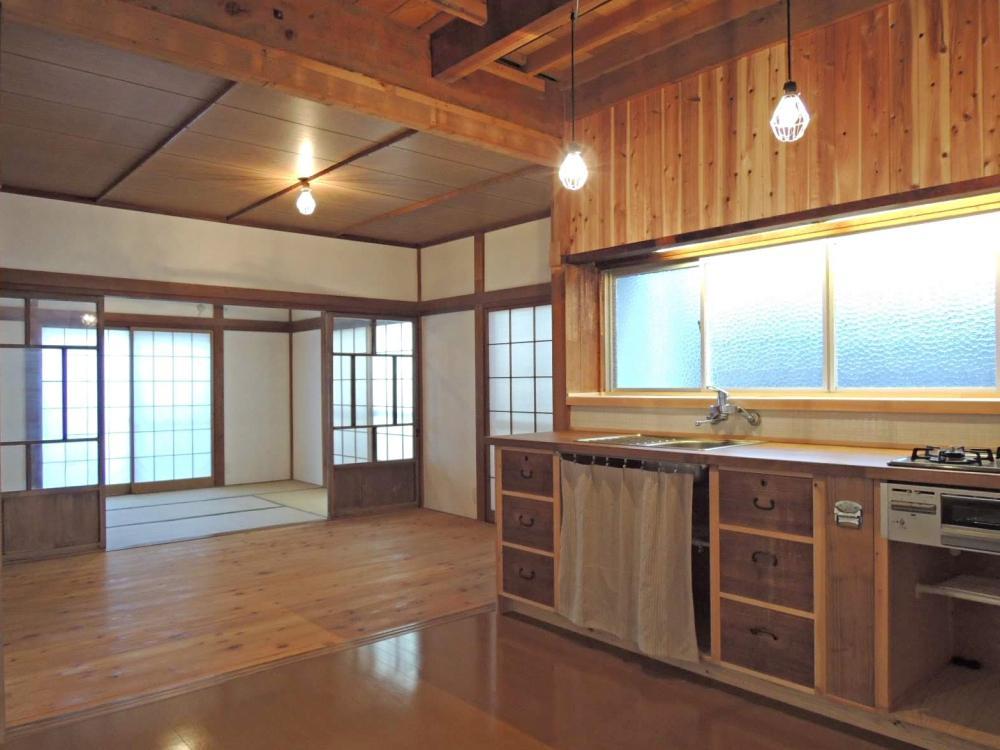 手前からLDKから和室までひとつながりに。木のキッチンの正面壁には白い小さなタイルが貼られています。