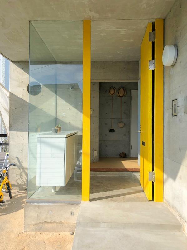 黄色の玄関扉とガラス張りの玄関ホール。