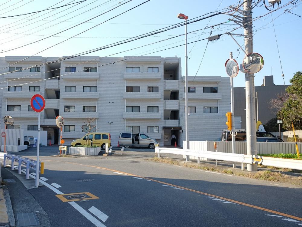マンションはバス通りに面しています。敷地内駐車場は空あり。