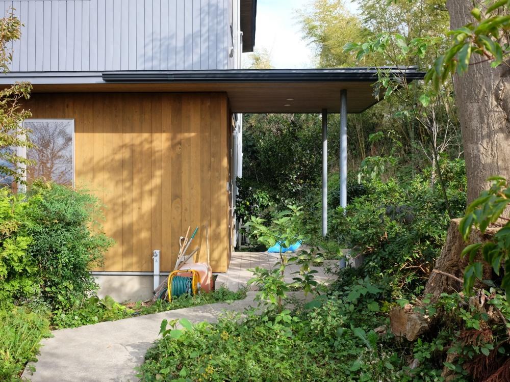 アプローチの先にあらわれる板張りの玄関。広い庭では菜園も楽しめます。