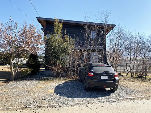 ちょこんとしたボリュームの愛おしくなる感じの建物、手前が砂利敷の駐車スペース
