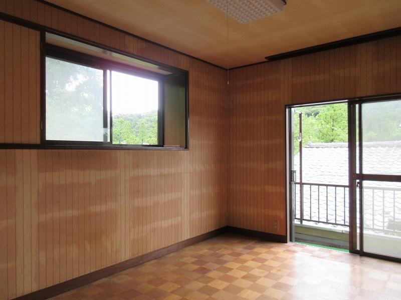 2階の洋室。窓の外には山の緑と空が広がる
