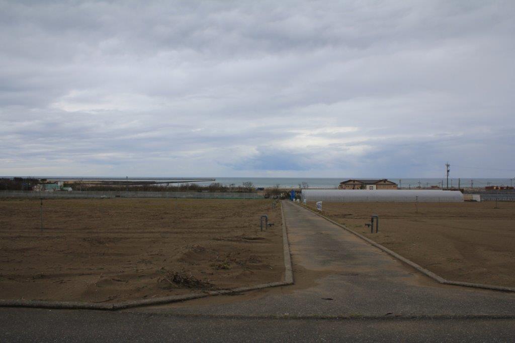 防風林を越えたところからの景色。目の前の海はこの時期サーファー多い内灘海岸。左側の堤防は大浜釣り公園