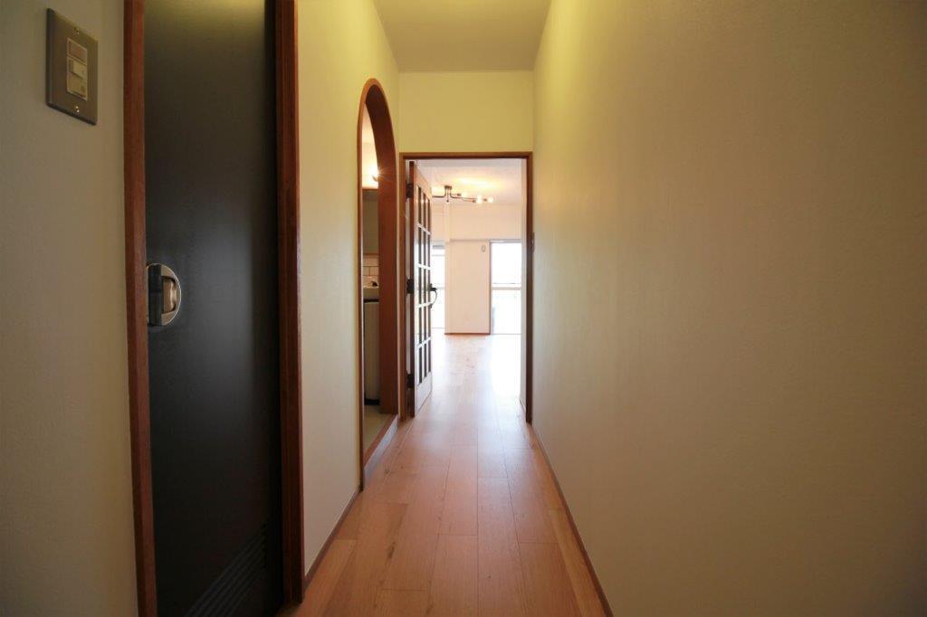 無垢のフローリングの廊下。メカっぽいドアノブや楕円の開口がアクセントに