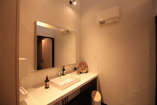 天井が高いモダンな化粧台とトイレ。