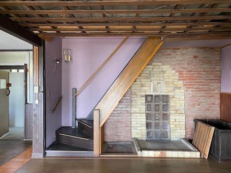 薪ストーブ置き場。使い込まれたレンガと薄紫壁の退廃美。
