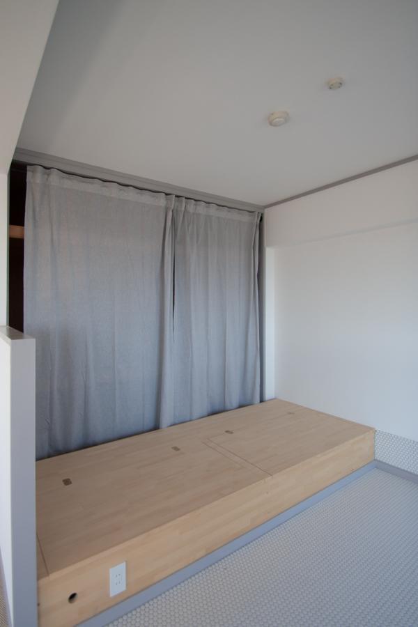 収納付きベッドは備え付け。押し入れはカーテンでサラッと目隠し。