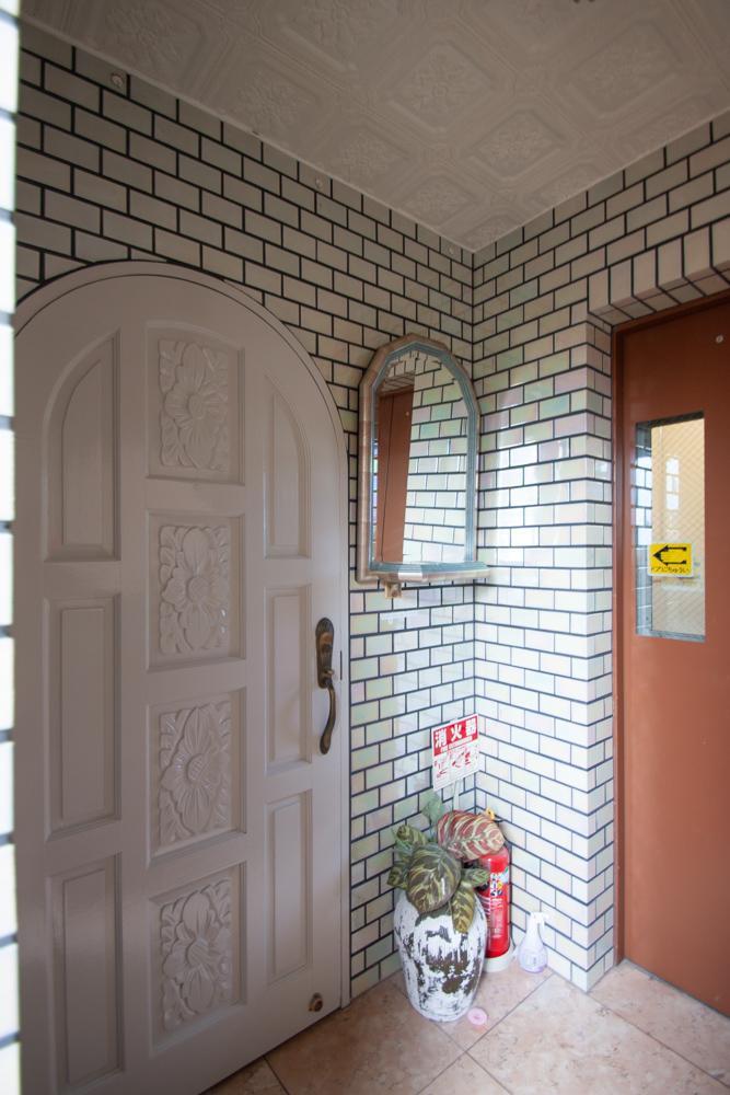 タイルの壁とアーチの玄関扉