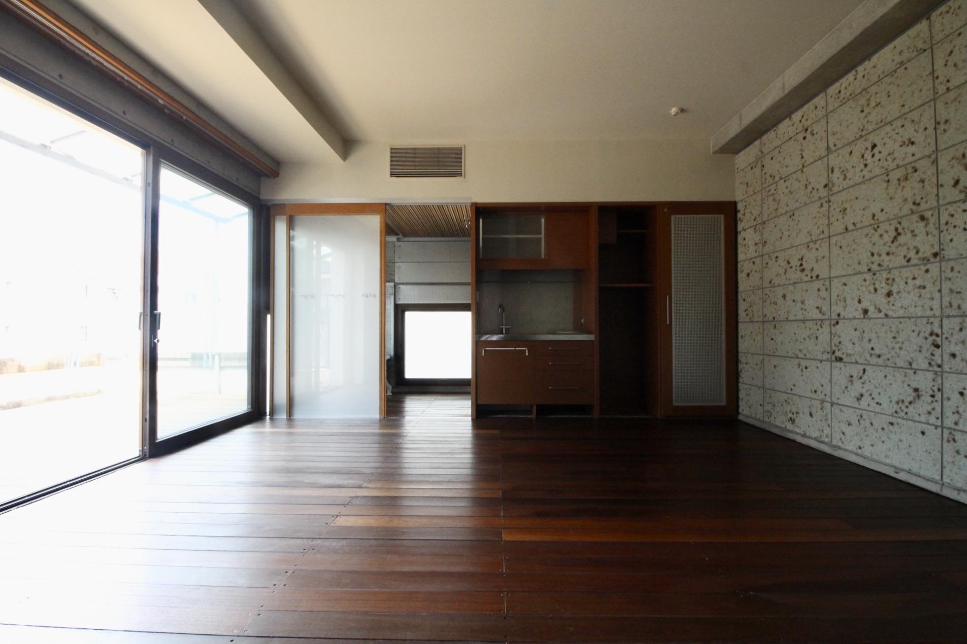 室内にも石壁を使用し、木製サッシの大開口窓からバルコニー兼玄関へフラットに繋がる