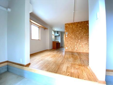 土間から無垢材フローリングへと伸びる空間。合板壁が良きアクセント。