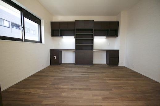 リビング脇の洋室はダーク色の無垢材空間