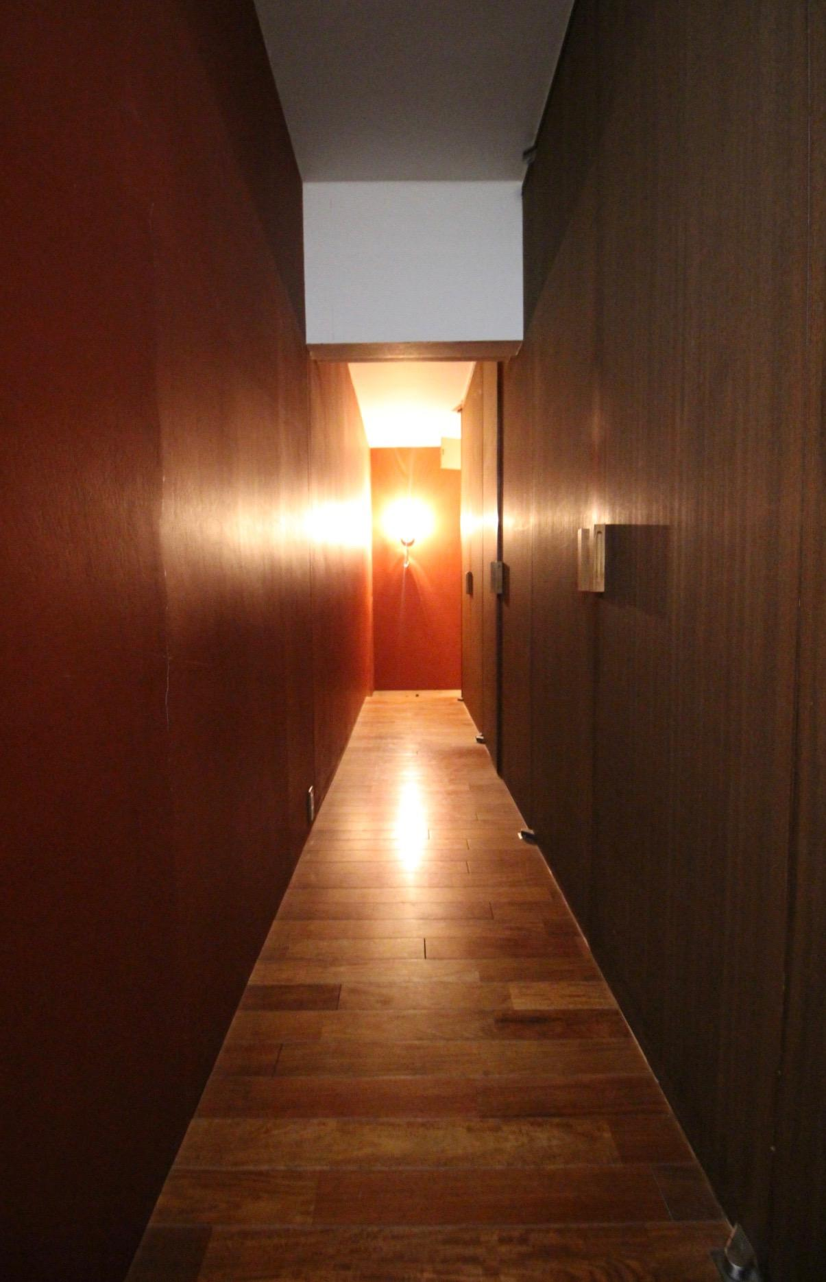 玄関を入ると暗めの間接照明とズラリとクローゼットがお出迎え