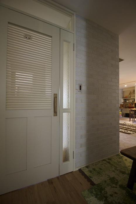 タイル壁と白ルーバー建具のコントラスト
