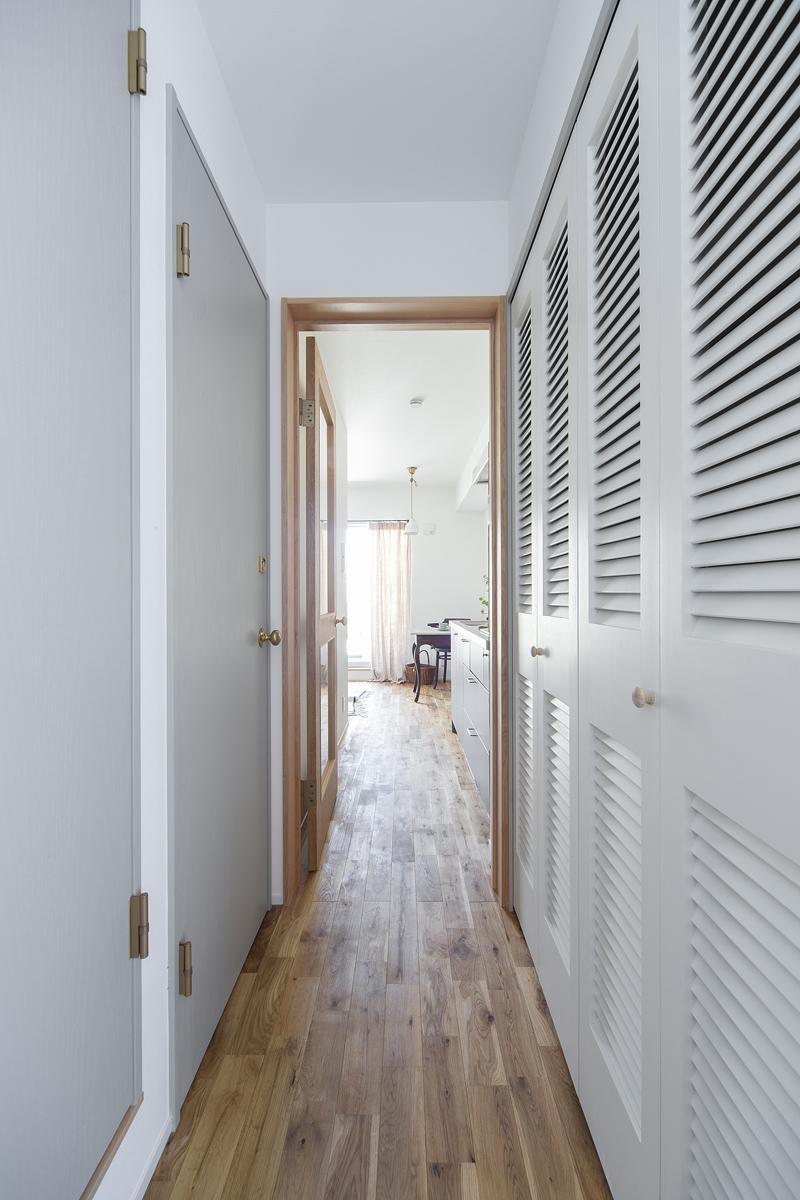 廊下とルーバー収納建具、グレイのドアが洗面トイレへ