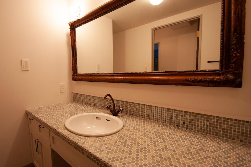 タイル張りの洗面台。アンティークの大きな鏡も