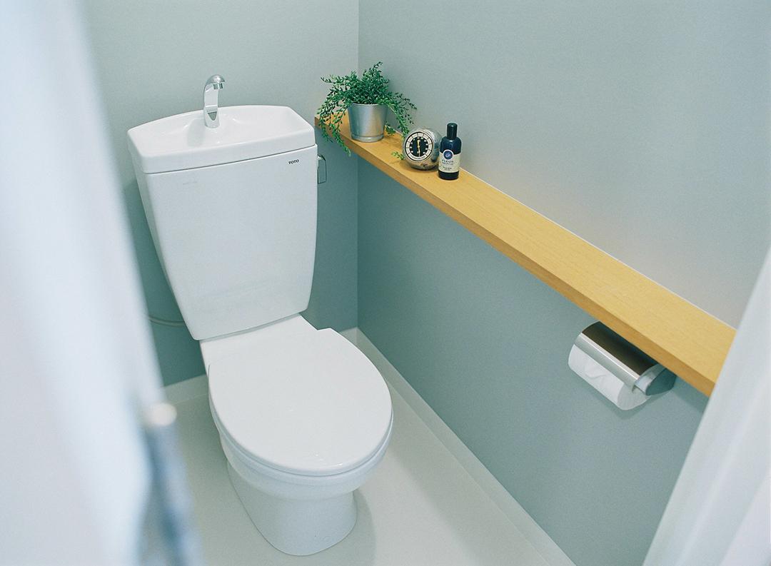 四方をグレーのカラークロスで仕上げた落ち着いた印象のトイレ。