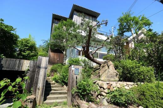 モダンなフォルムを切り裂く杉板壁と岩山のような庭