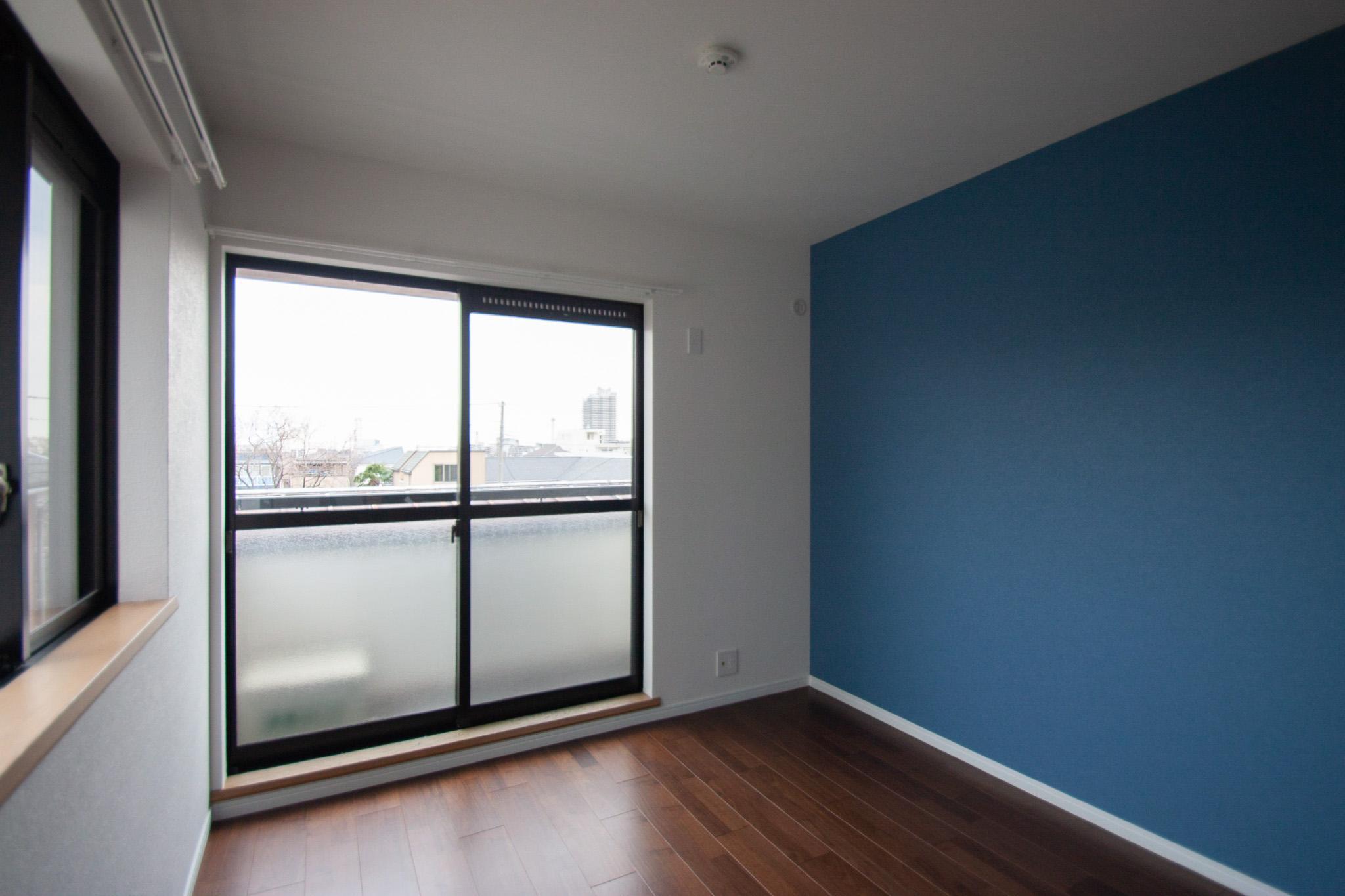 ブルーのアクセントクロスが貼られた寝室
