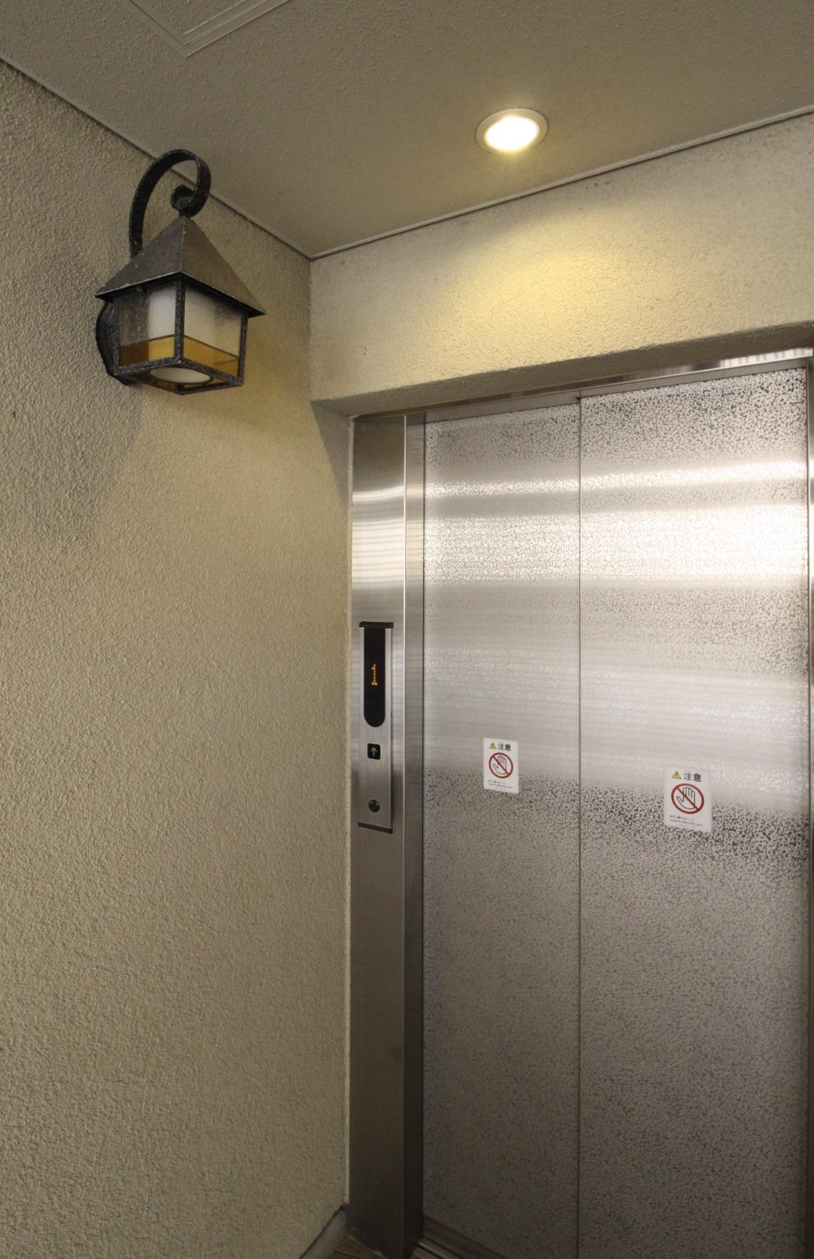 エレベーター前のレトロなステンドガラスの照明