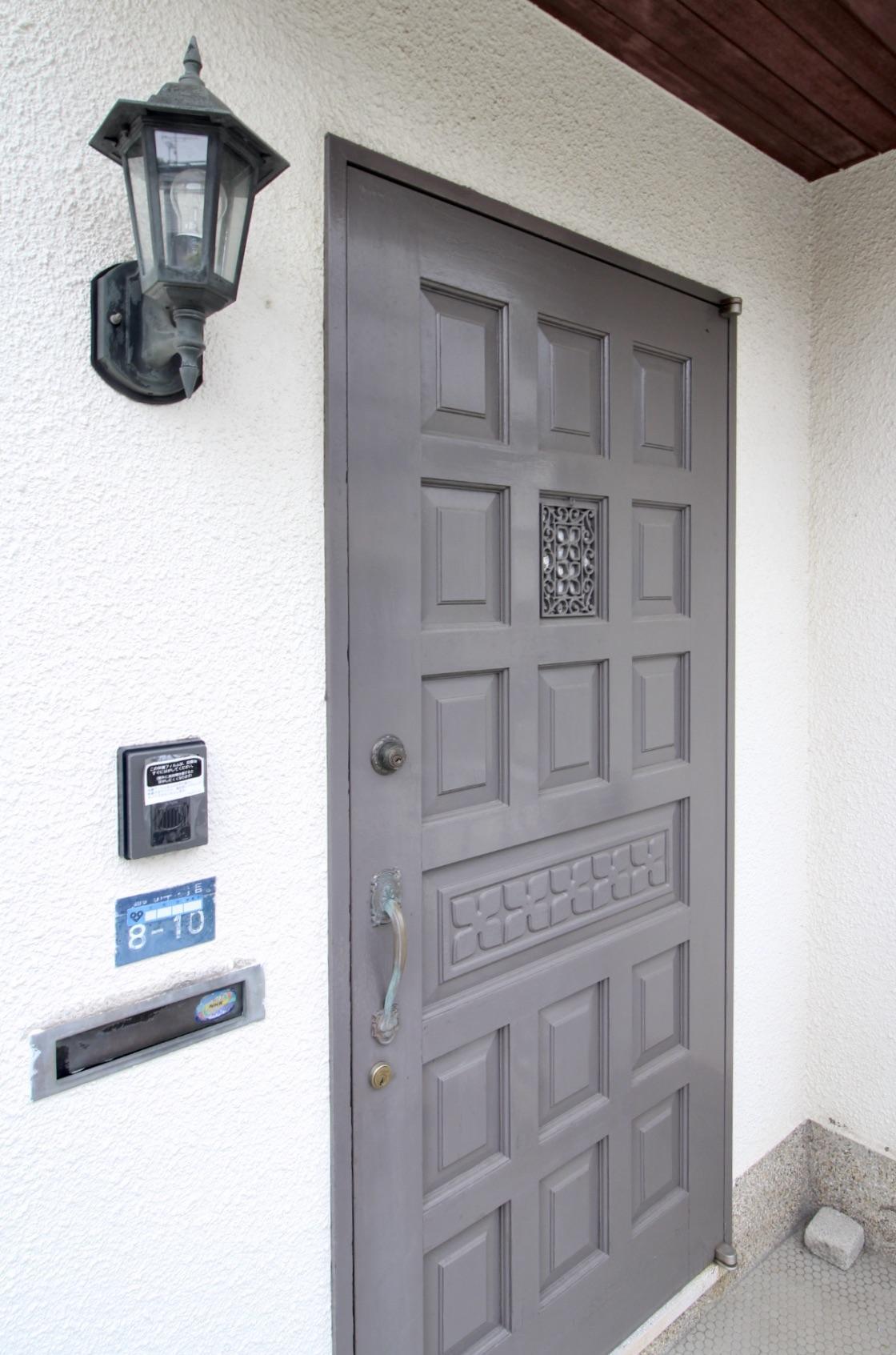ブルーグレーの木製ドアや照明、ポストがレトロで愛らしい
