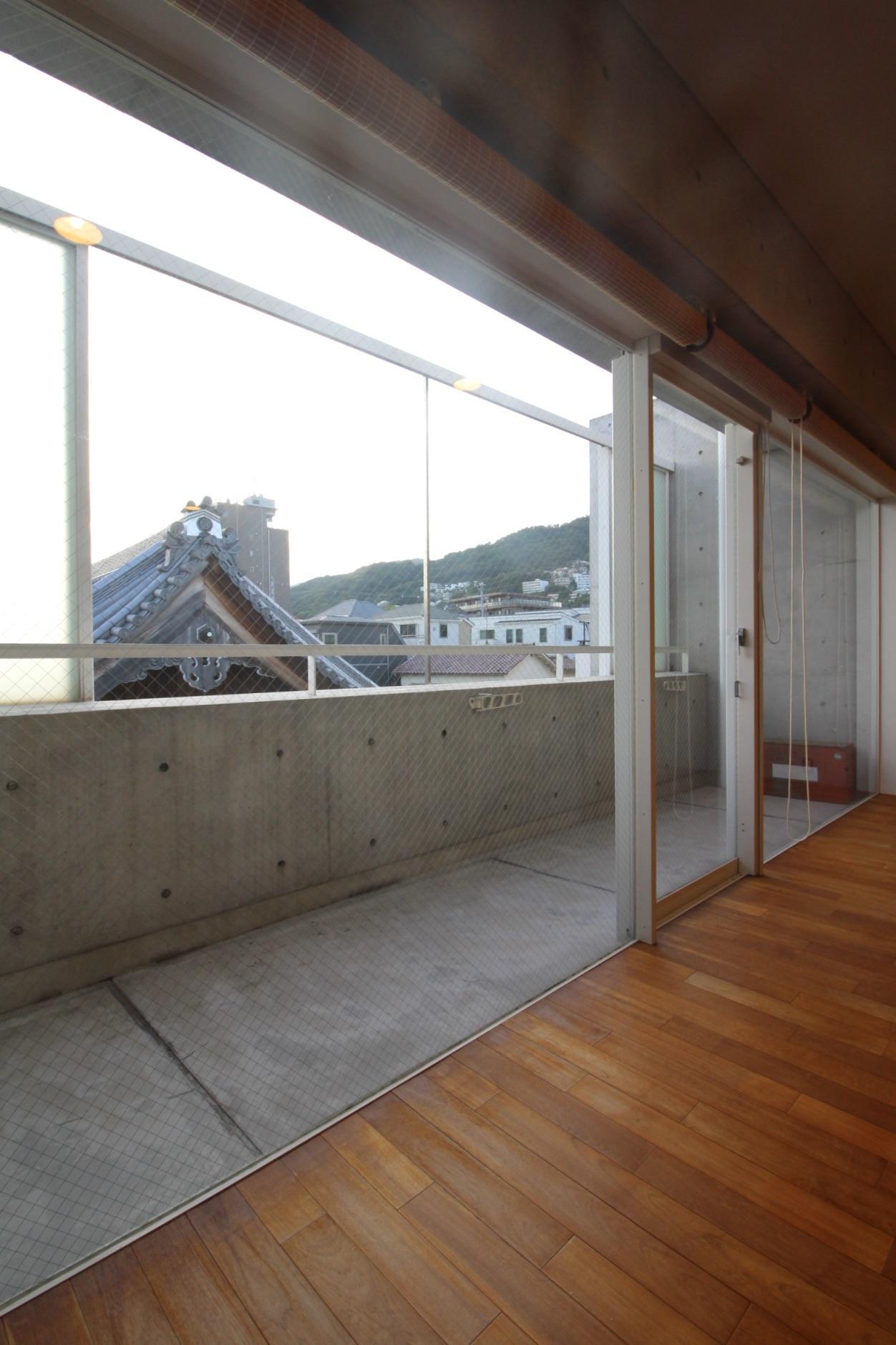 バルコニーの開閉可能な擦りガラス窓を開けると、山とダイナミックなお隣の寺の屋根瓦