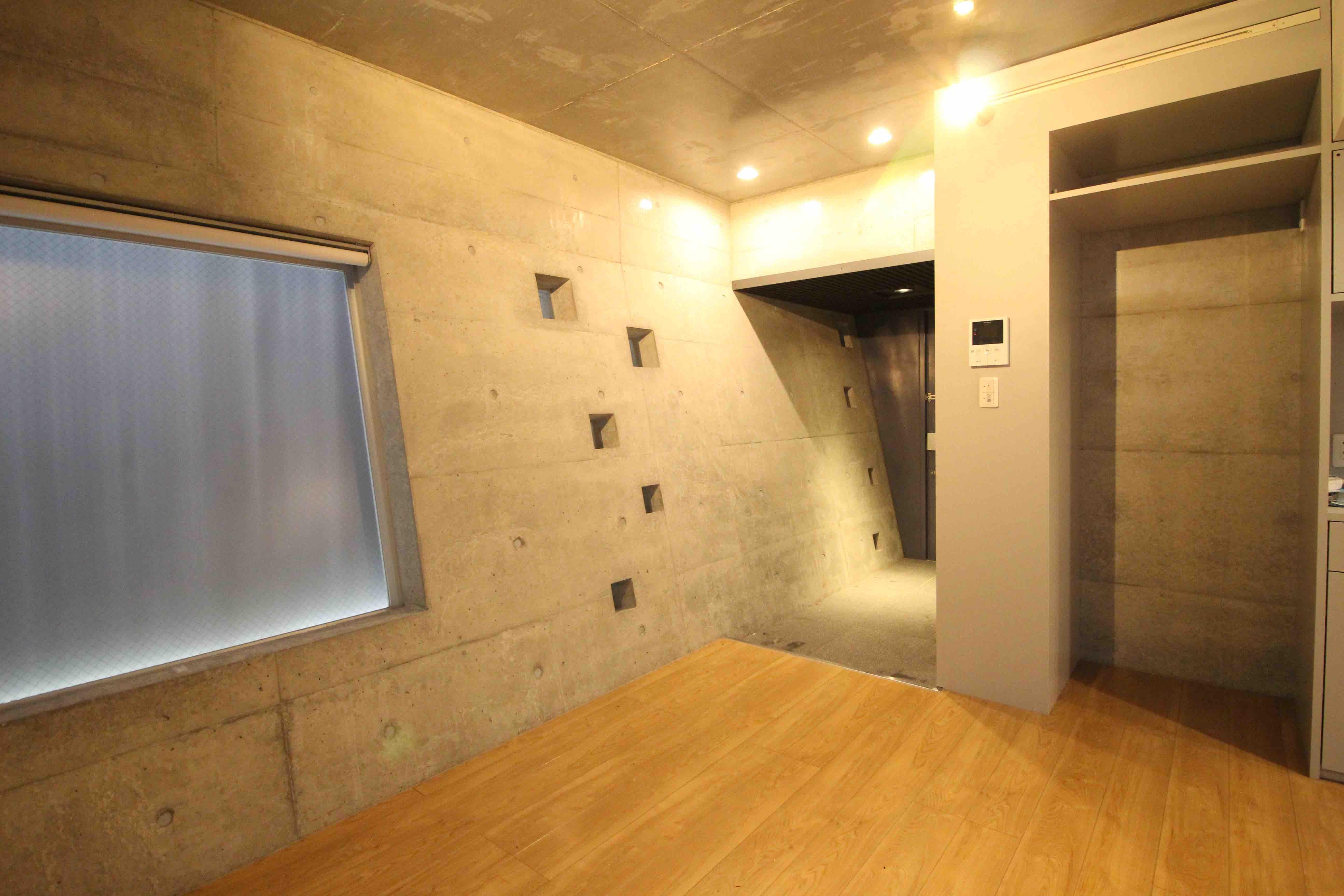 1階玄関、コンクリートの壁はあえて斜めです。