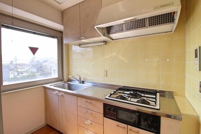 明るいキッチン、背後に冷蔵庫と洗濯機置き場があります(303号室)