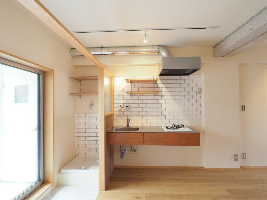 キッチンの横は洗濯機置き場。壁や床のタイルがアクセント。